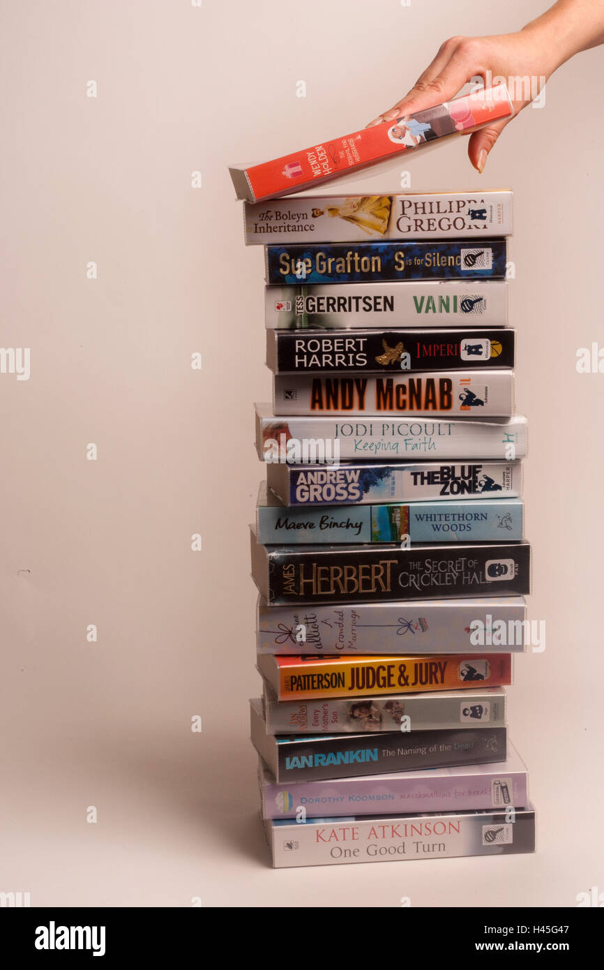 A stack of paperback books on a plain background. - Stock Image