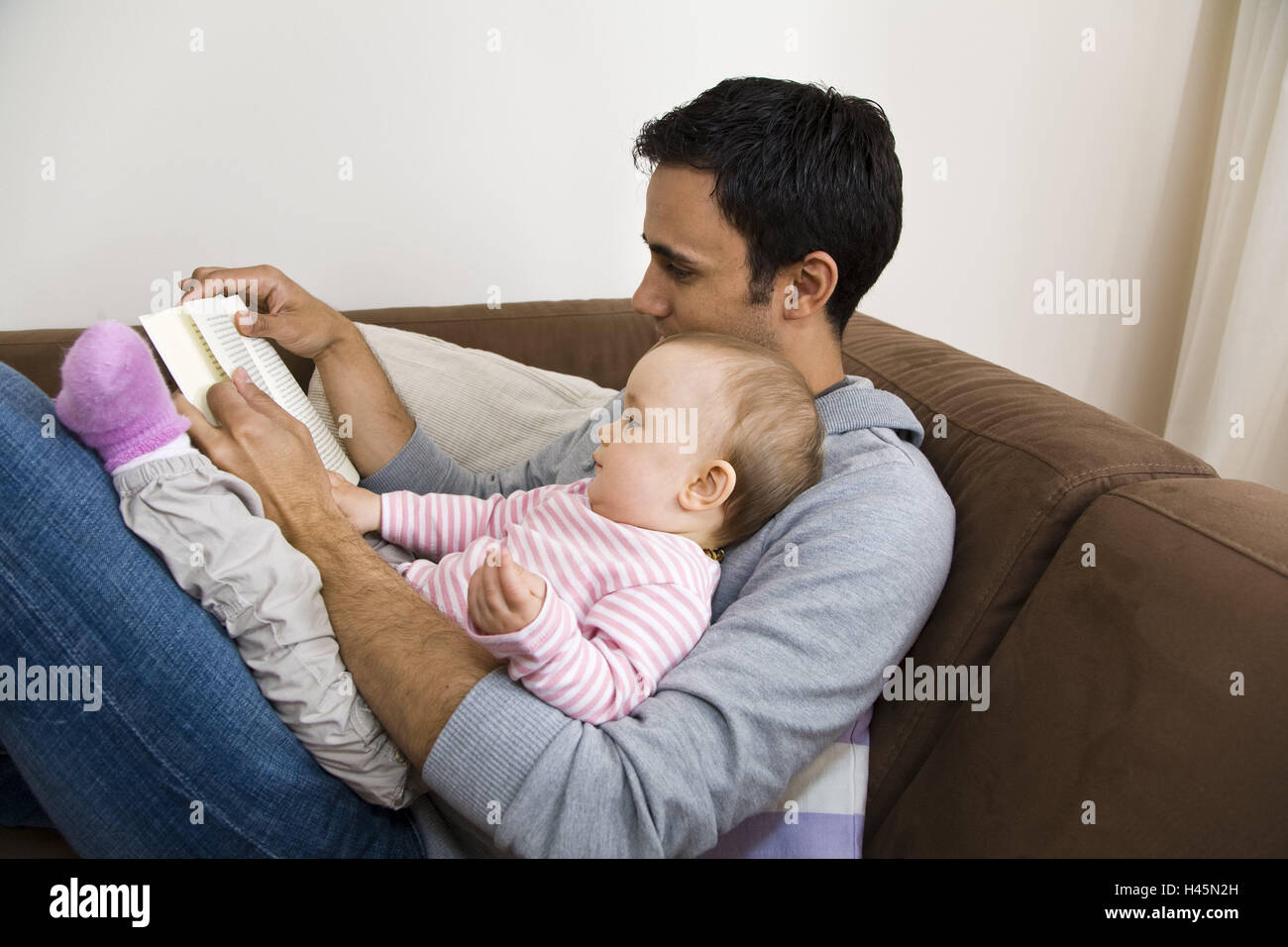 father baby read infant book family read man sofa trust