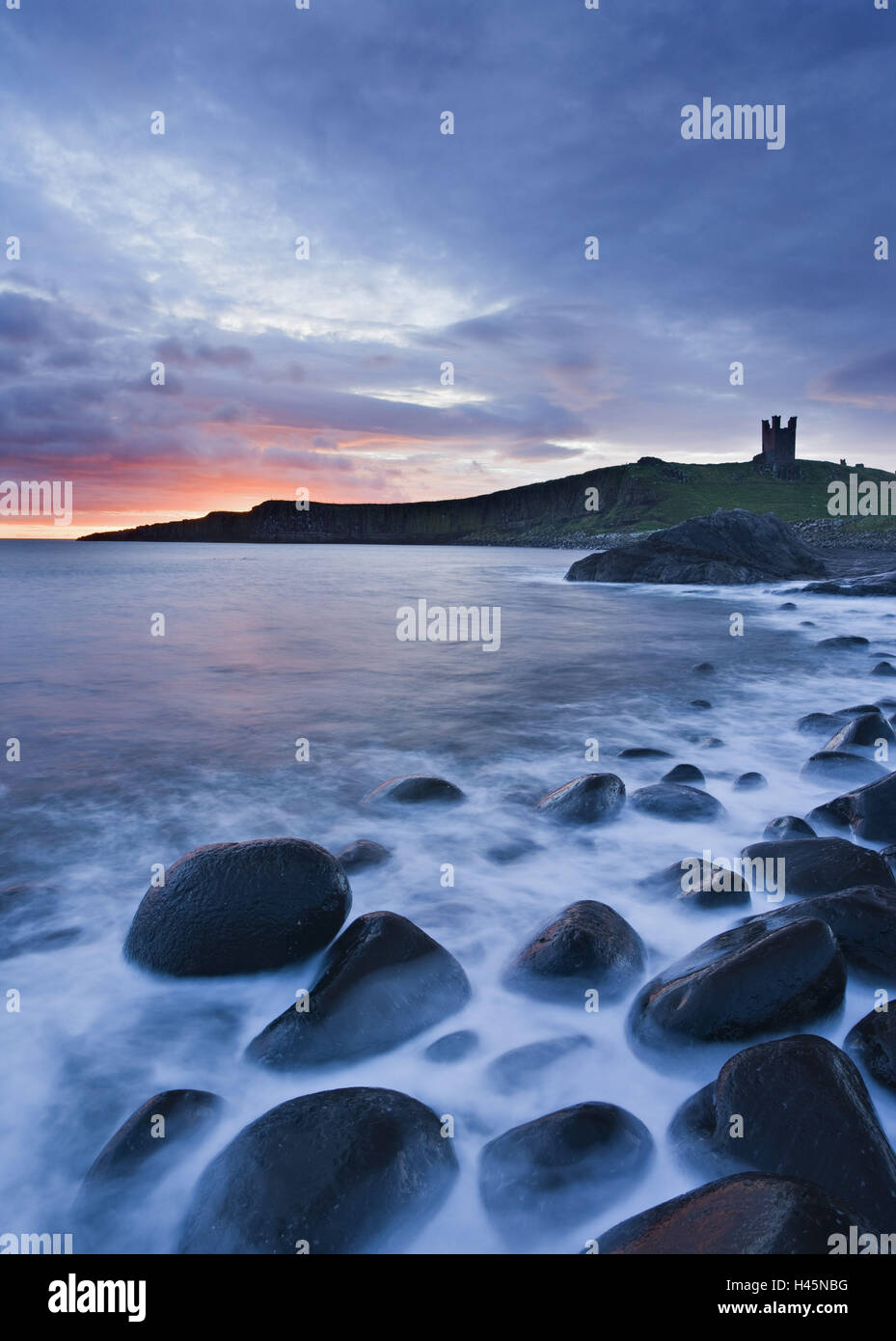 Great Britain, England, Northumberland, Dunstanburgh Castle, sea, stones, dusk, - Stock Image