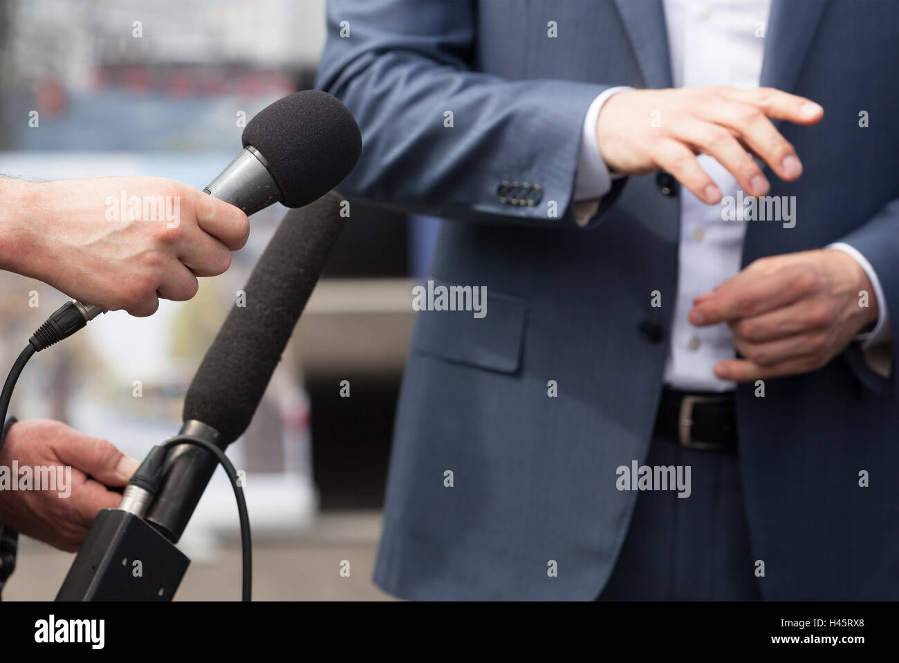 Reporters making interview with businessperson, politician or spokesman. News conference. - Stock Image