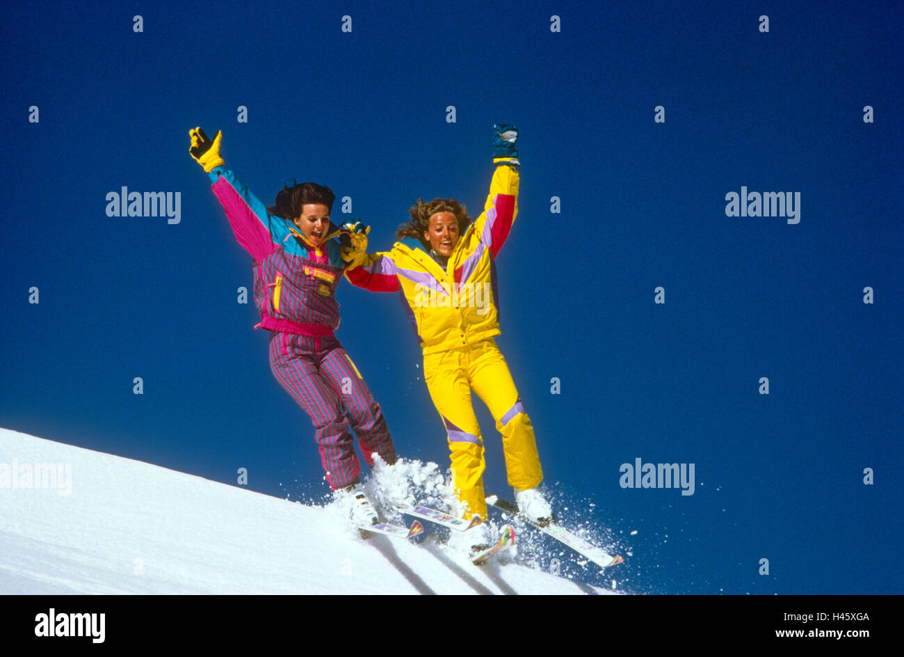 Two girls jumping on Ski's together - Stock Image