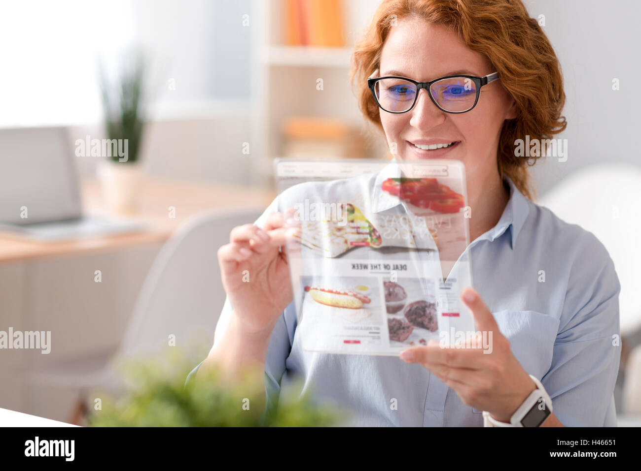 Positive woman using tablet - Stock Image