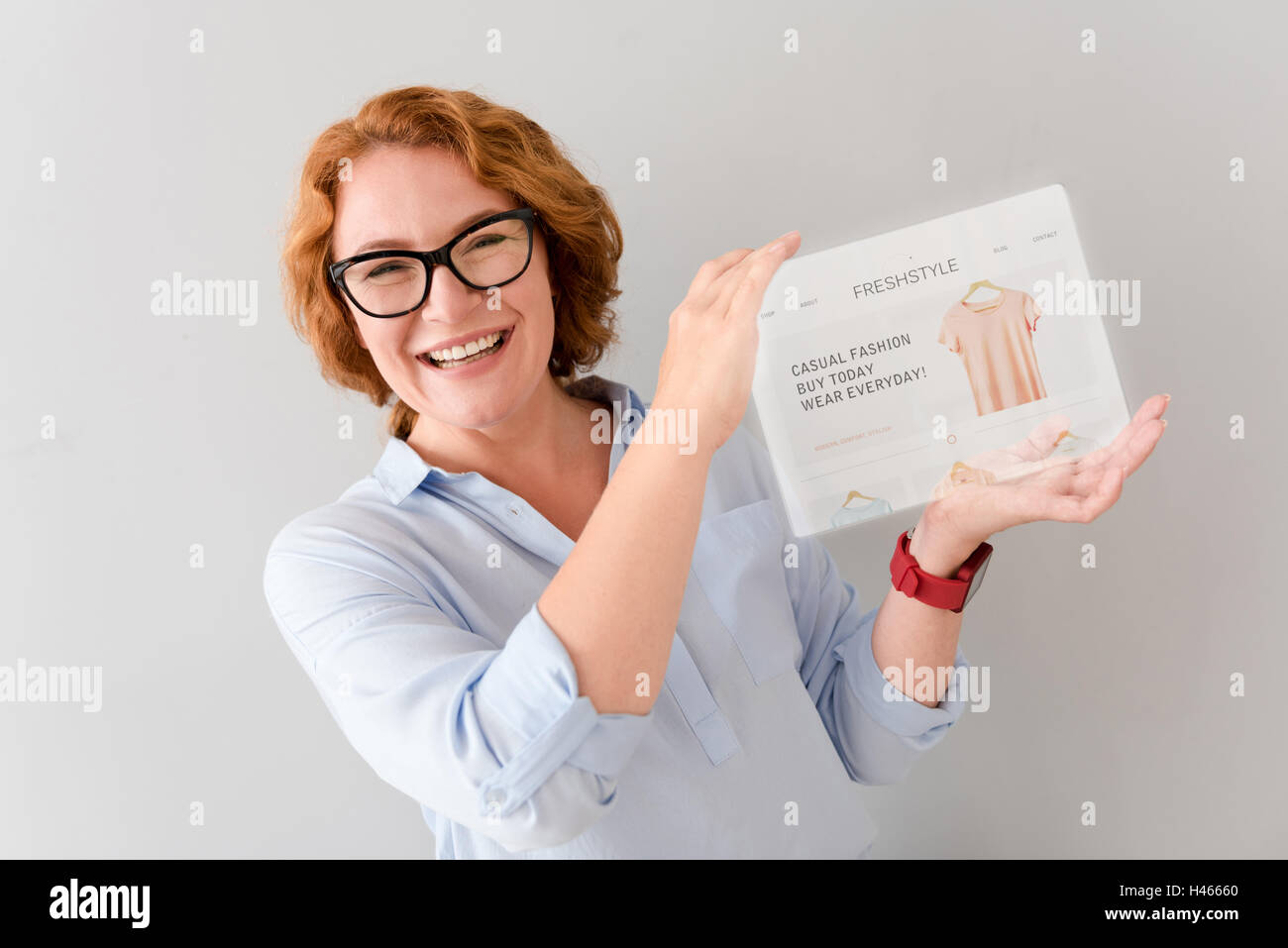 Overjoyed smiling womna showing tablet - Stock Image