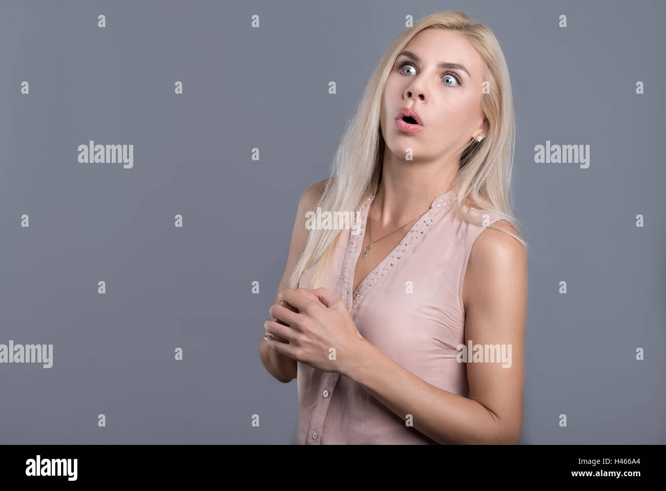 Confused and surprised beautiful woman opening mouth - Stock Image