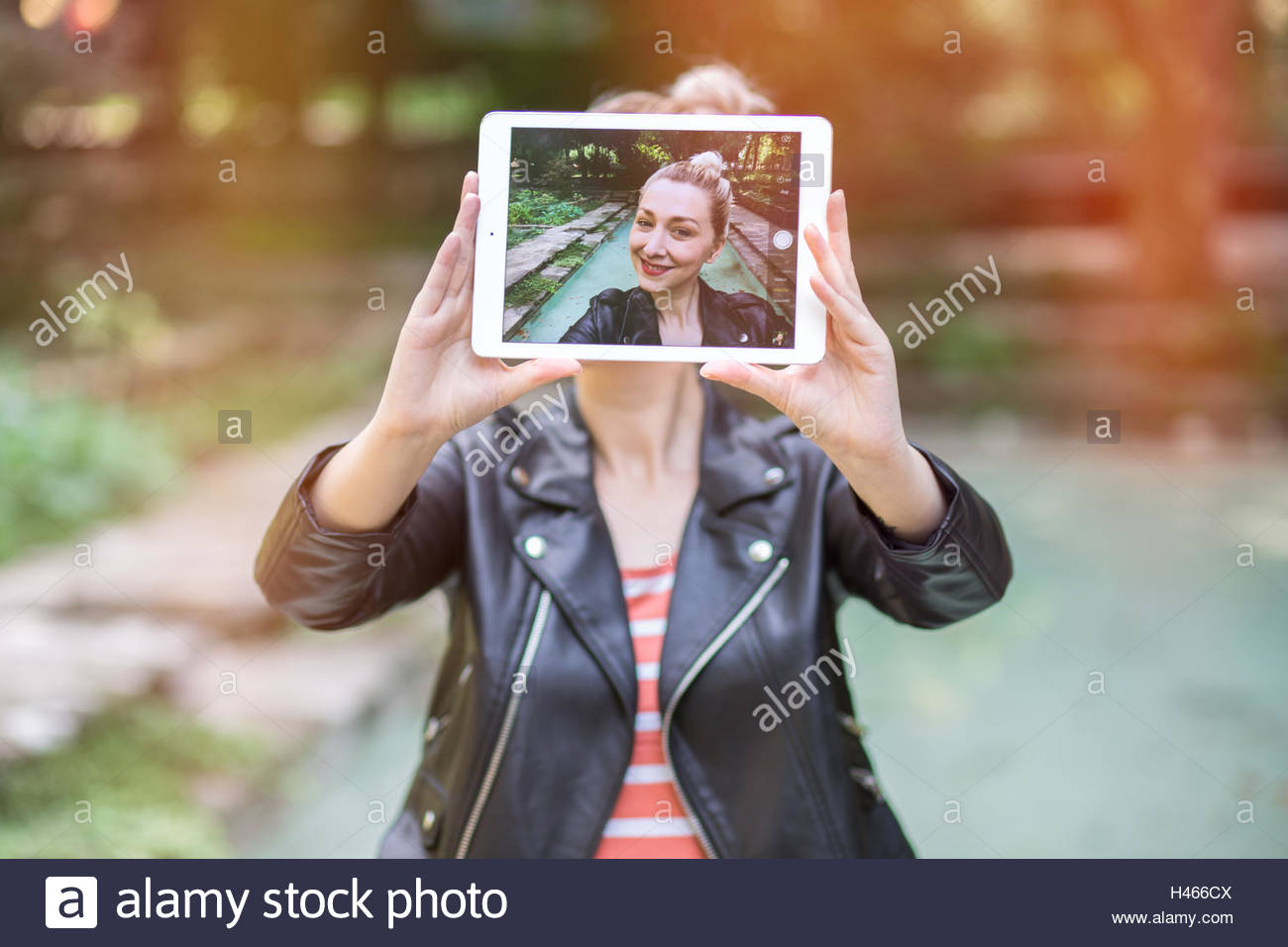 beautiful young woman taking a selfie with her tablet. focus on the screen. graded with a flare, in instagram style - Stock Image