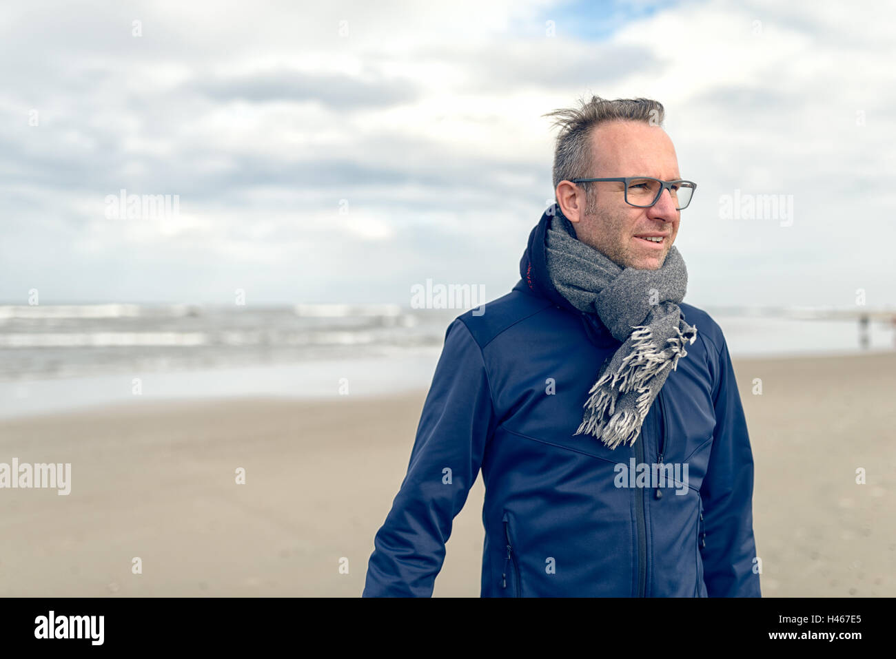 Irritated middle-aged man wearing glasses and a knitted woollen scarf standing on a deserted autumn beach on a cloudy - Stock Image