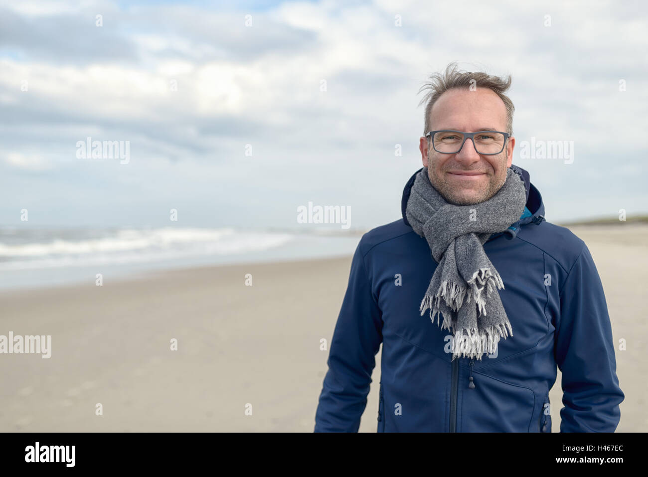 Smiling middle-aged man wearing glasses and a knitted woollen scarf standing on a deserted autumn beach on a cloudy - Stock Image