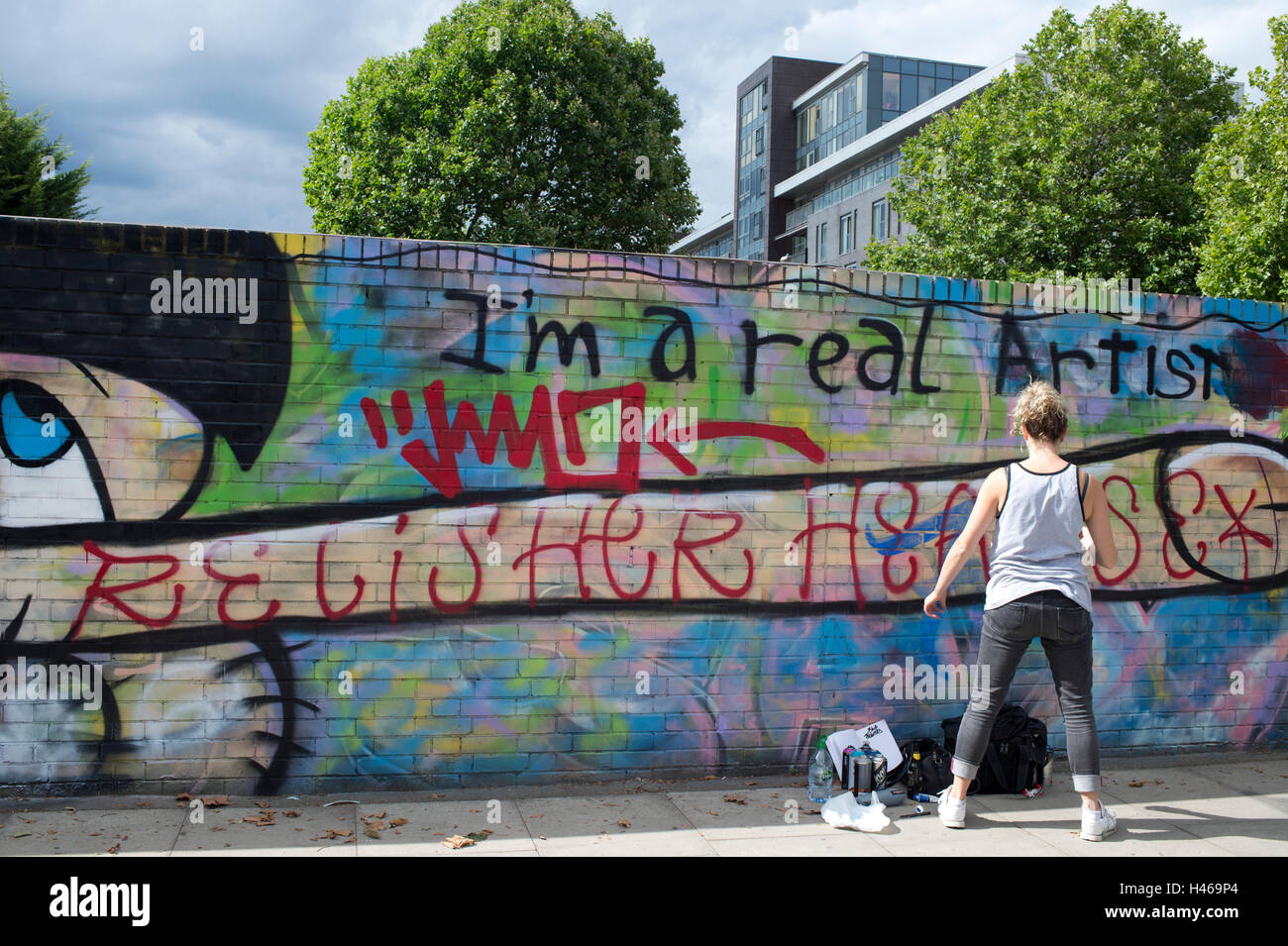 Hackney Wick. Woman painting on a wall - anti gentrification. - Stock Image
