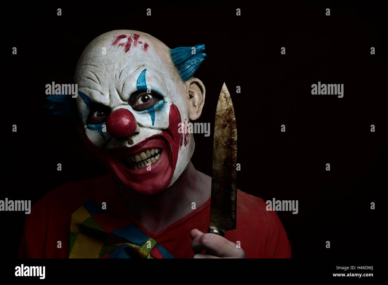 a scary evil clown with a big knife in his hand, against a dark background - Stock Image