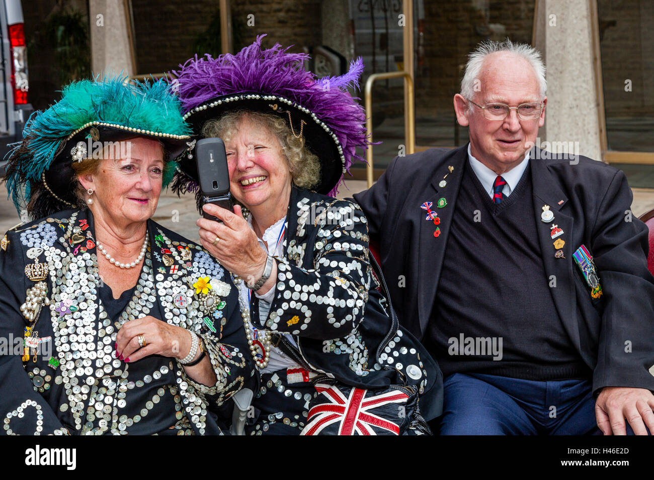 Two Pearly Queens Pose For A Selfie At The Pearly Kings and Queens' Harvest Festival, The Guildhall Yard, London, Stock Photo