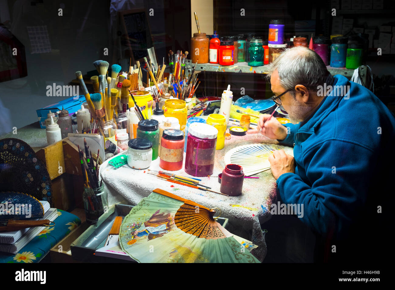 Craftsman hand decorating spanish fans in his workshop - Stock Image