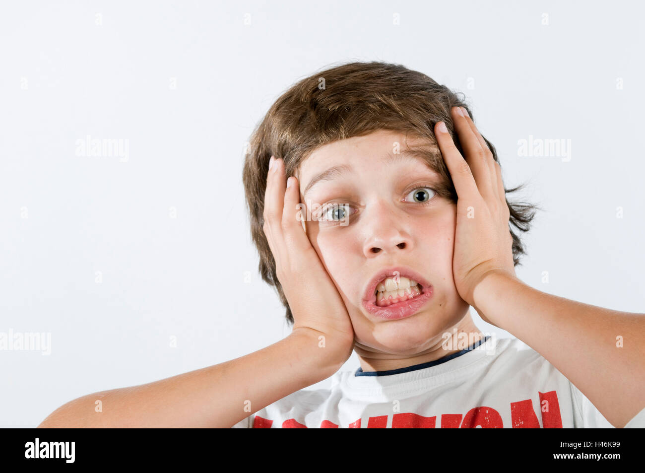 Ten-year boy presses palms on his cheeks with astonished face before white background. - Stock Image