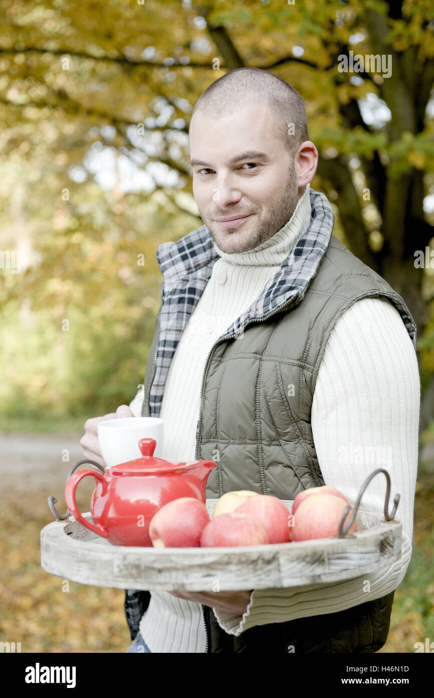 Man serves apples and tea on tablet, - Stock Image