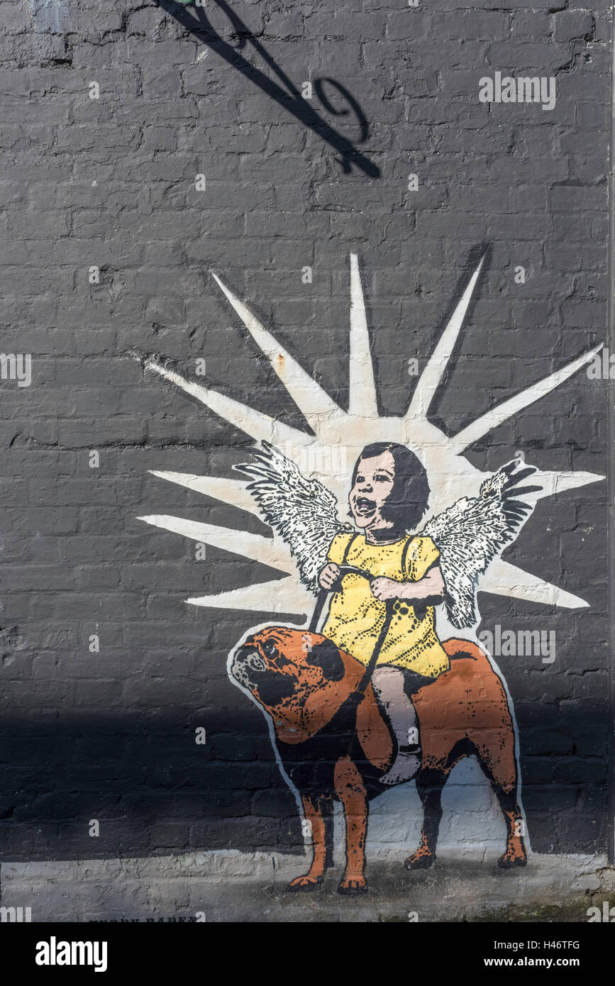A street artist has painted an angelic child sitting on top of a small dog in the old town in Margate, Kent. - Stock Image