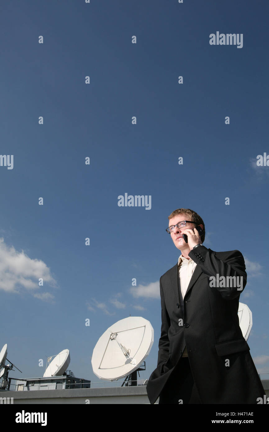 Businessman, call up seriously, mobile phone, half portrait, building, parabolic antennae, business, roof, house - Stock Image