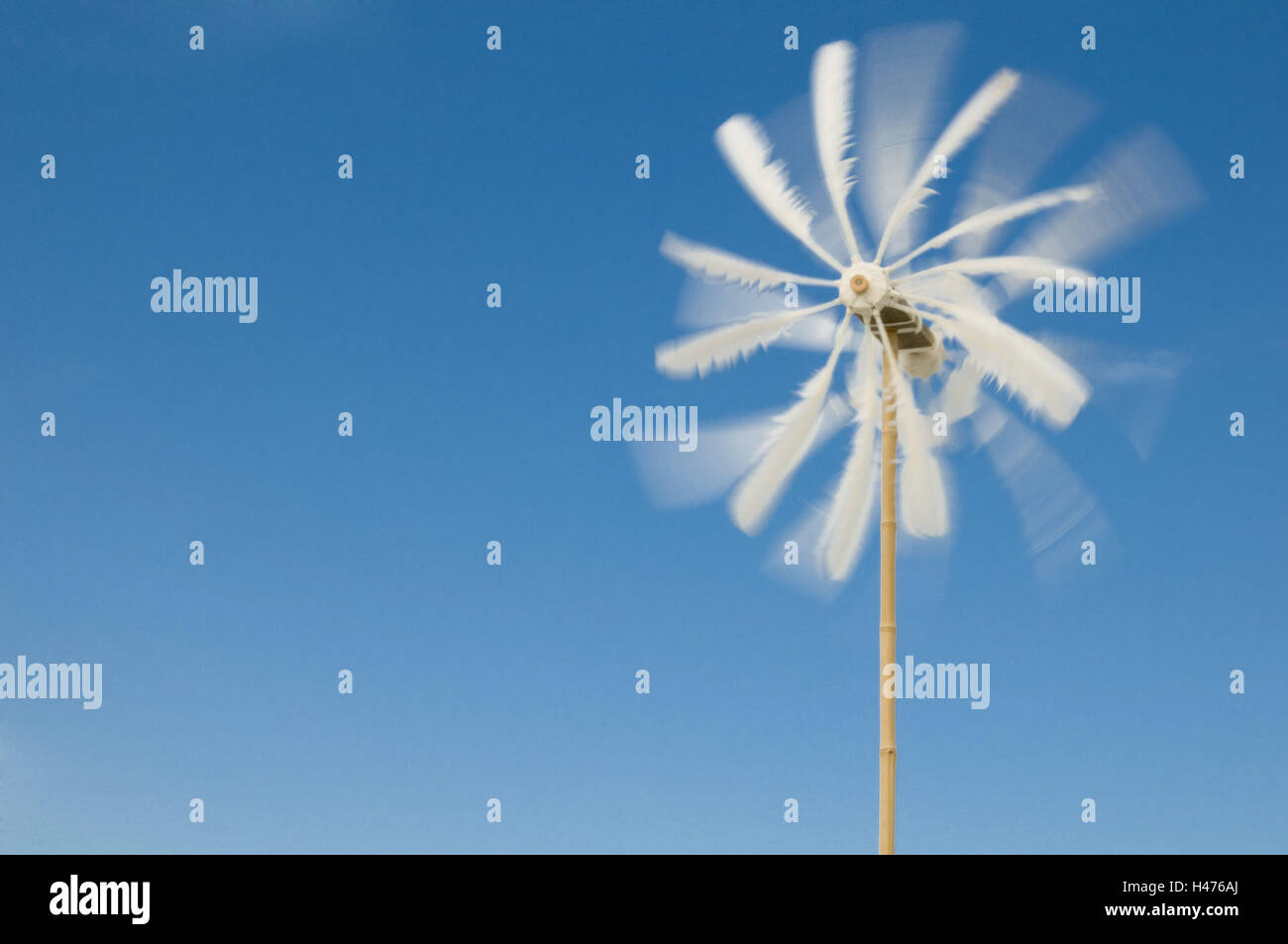 Pinwheel made of feathers rotates against bright blue sky, - Stock Image