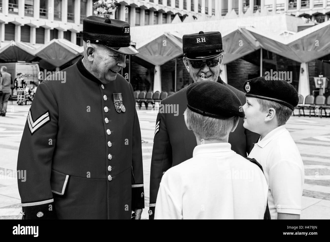 Two Chelsea Pensioners Talking To Young Sea Cadets At The Pearly Kings and Queens' Harvest Festival, The Guildhall, - Stock Image