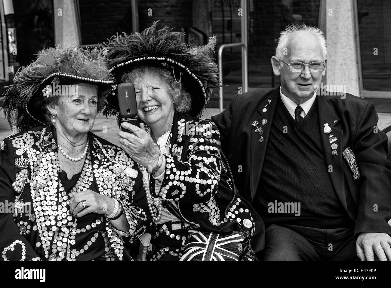 Two Pearly Queens Pose For A Selfie At The Pearly Kings and Queens' Harvest Festival, The Guildhall Yard, London, - Stock Image