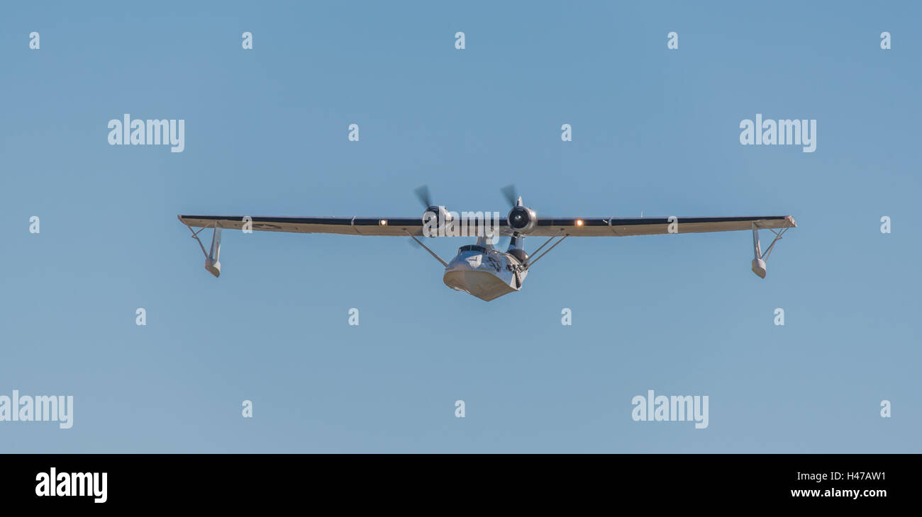 A Catalina seaplane catches the light as it turns, wingtip floats lowered, to run in for a water landing. - Stock Image
