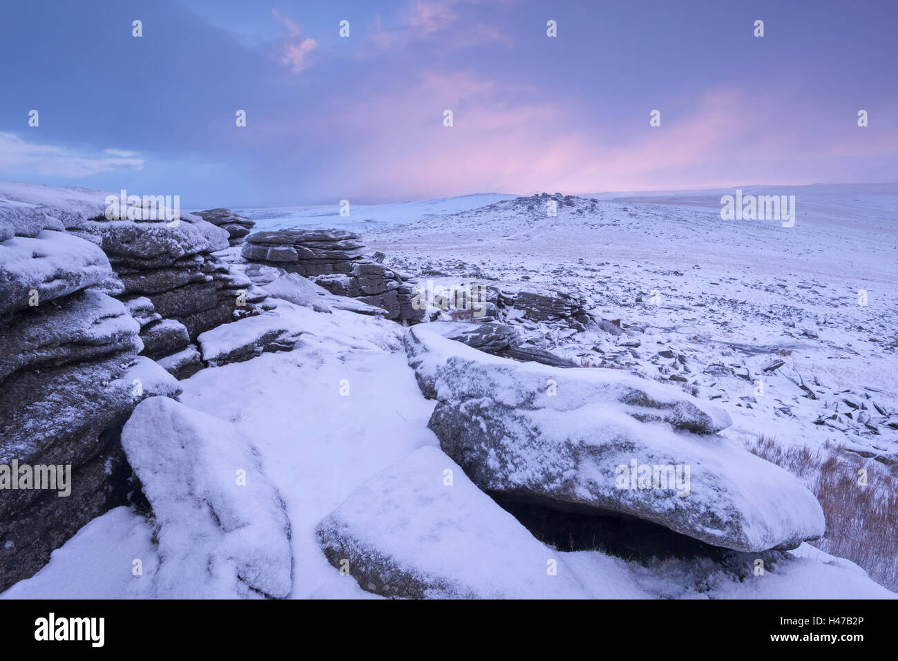 Dawn emerges over a snow covered moorland, Great Staple Tor, Dartmoor National Park, Devon, England. Winter (January) - Stock Image