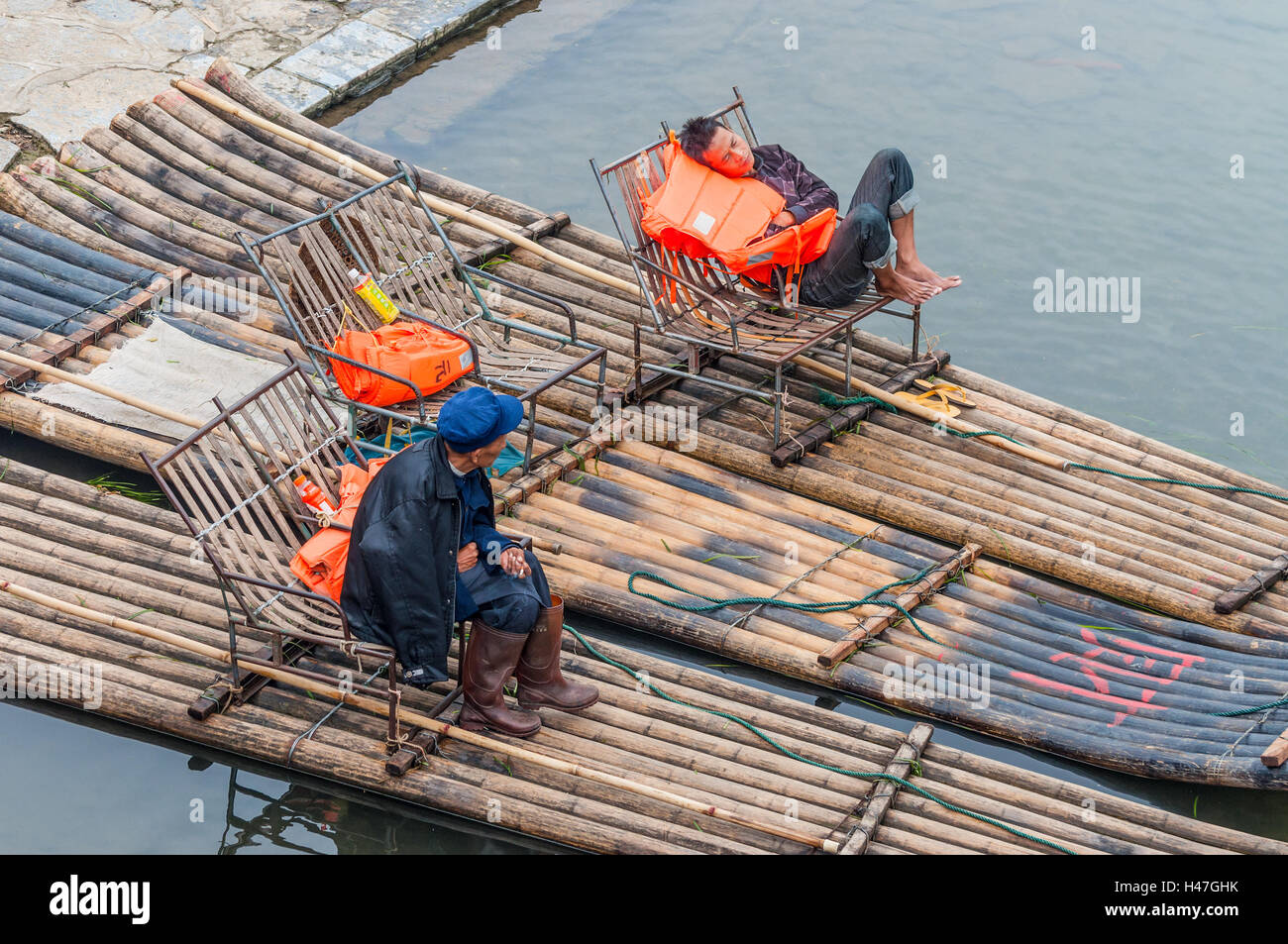 Boaters rest waiting for tourists on their bamboo raft on the bank of the Li River, Yangshuo - Stock Image