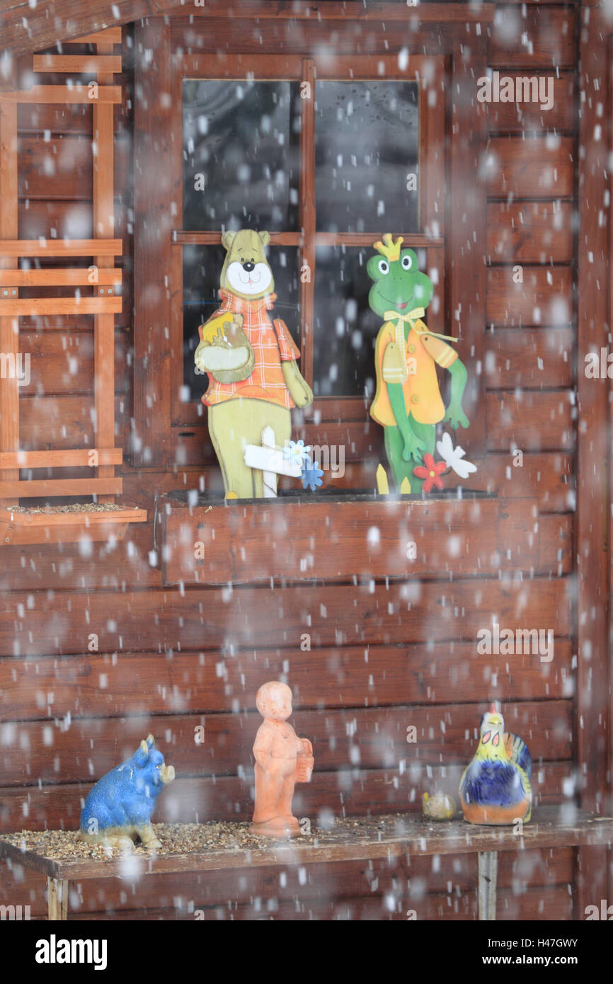 Summer house with figures in the snow beating out, - Stock Image