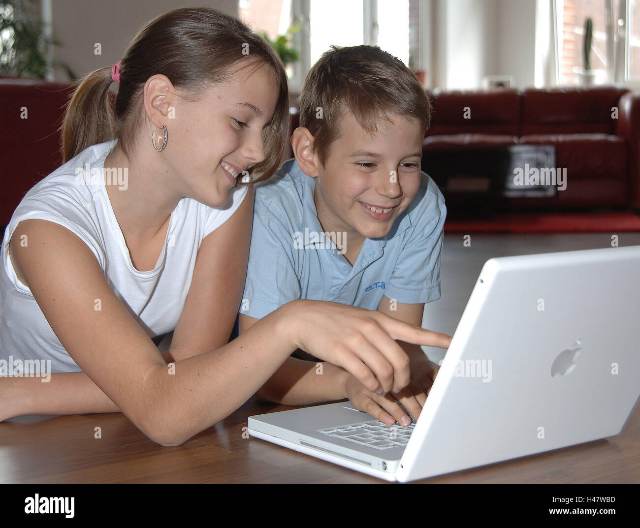 Girls, boy, notebook computer, Internet surfing, happy, people, children, siblings, brother, sister, friends, computers, - Stock Image