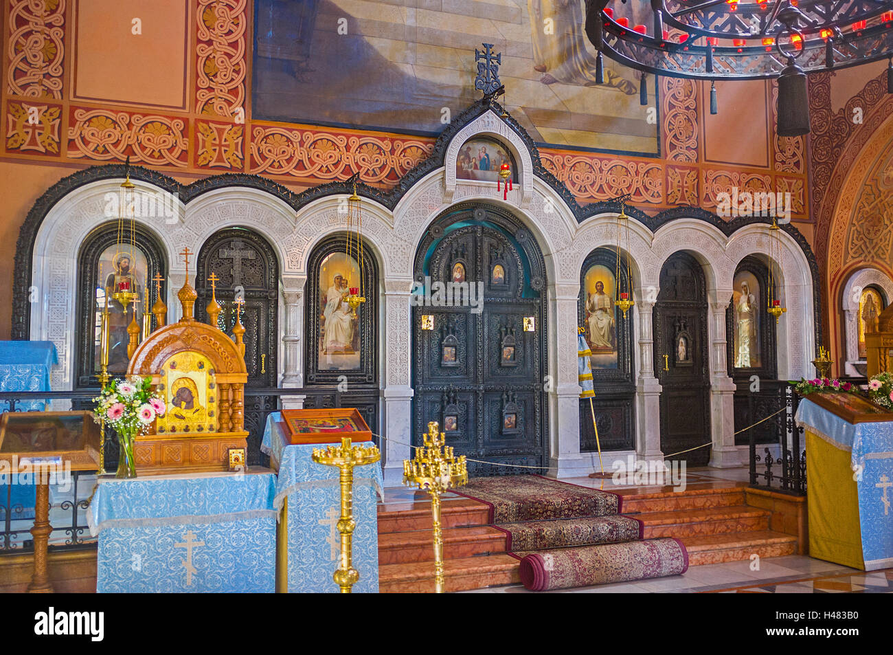 The iconostasis in Russian Orthodox Church of Mary Magdalene made of dark wood with white stone frames - Stock Image