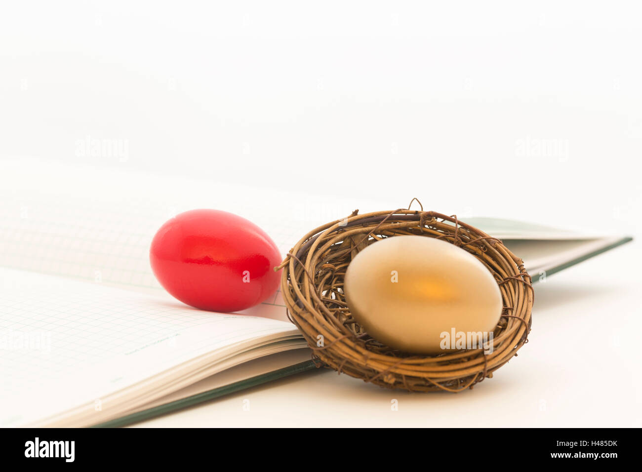 Red and gold nest eggs on green ledger reflect risk and opportunity in investment environment for businesses and - Stock Image
