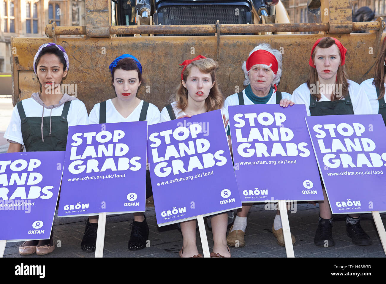 Oxfam employees dressed as land girls sit on a JCB outside the Houses of Parliament to highlight the problem of - Stock Image