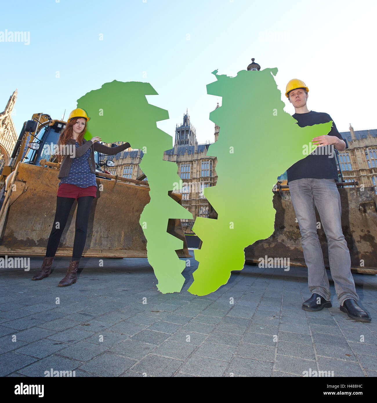 Oxfam employees pose with a map of Africa split down the middle to highlight the problem of land grabs - Stock Image