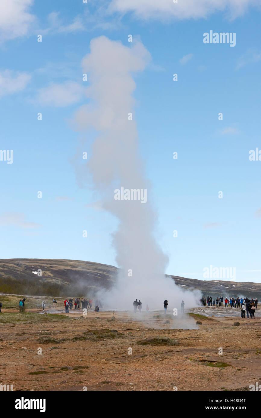 tourists stand around watching the strokkur geyser erupting geysir Iceland Stock Photo