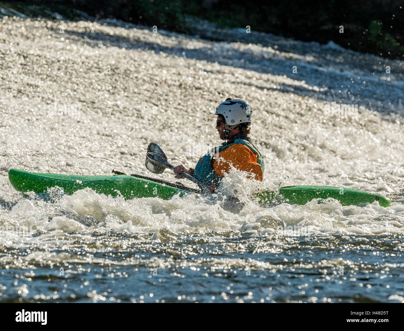 Male adult White Water Kayaking along a River Exe Weir on a bright Autumn day. Situated near Exeter in Devon, United - Stock Image