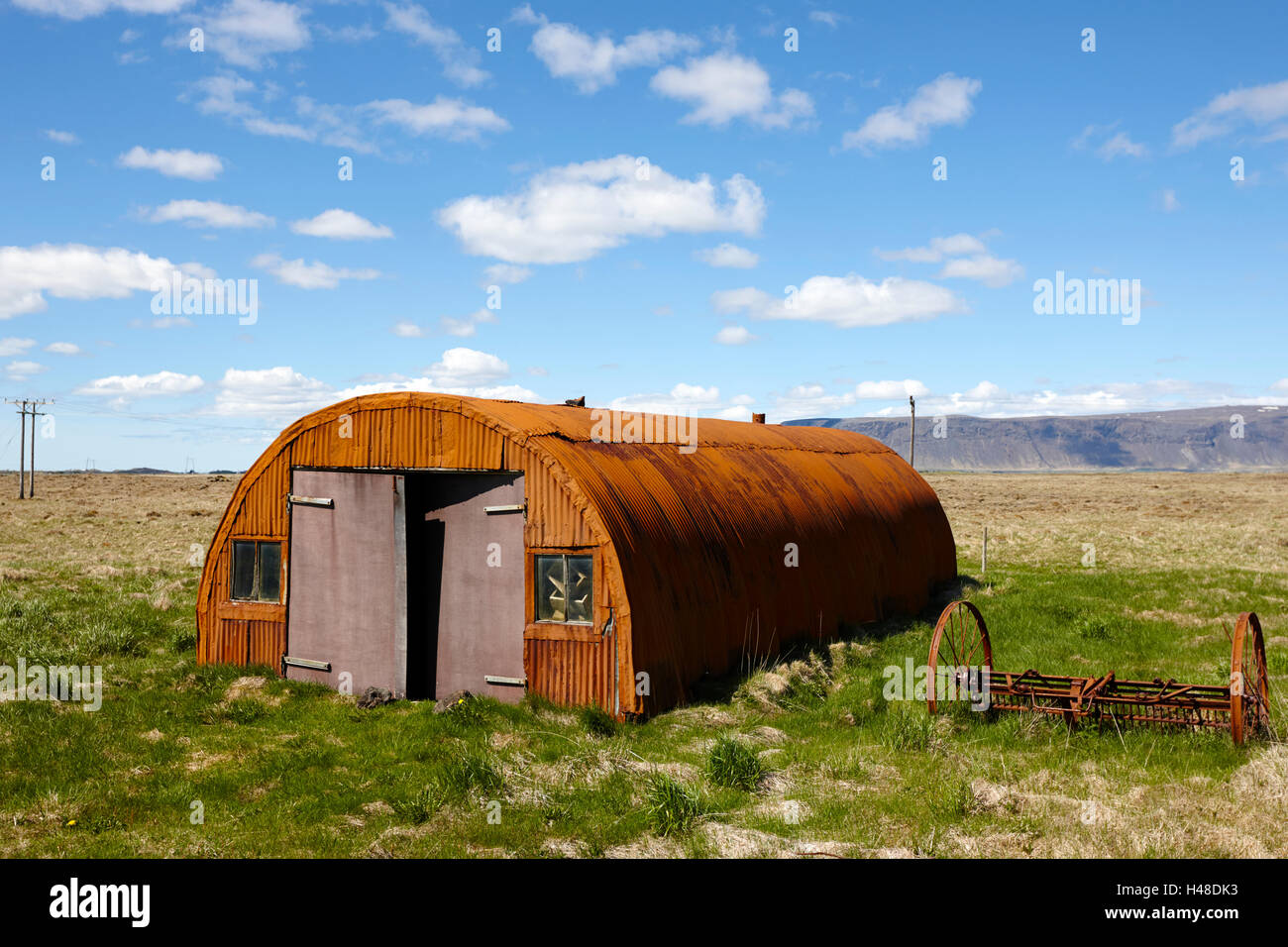 old rusting nissen hut on farmland in Iceland - Stock Image