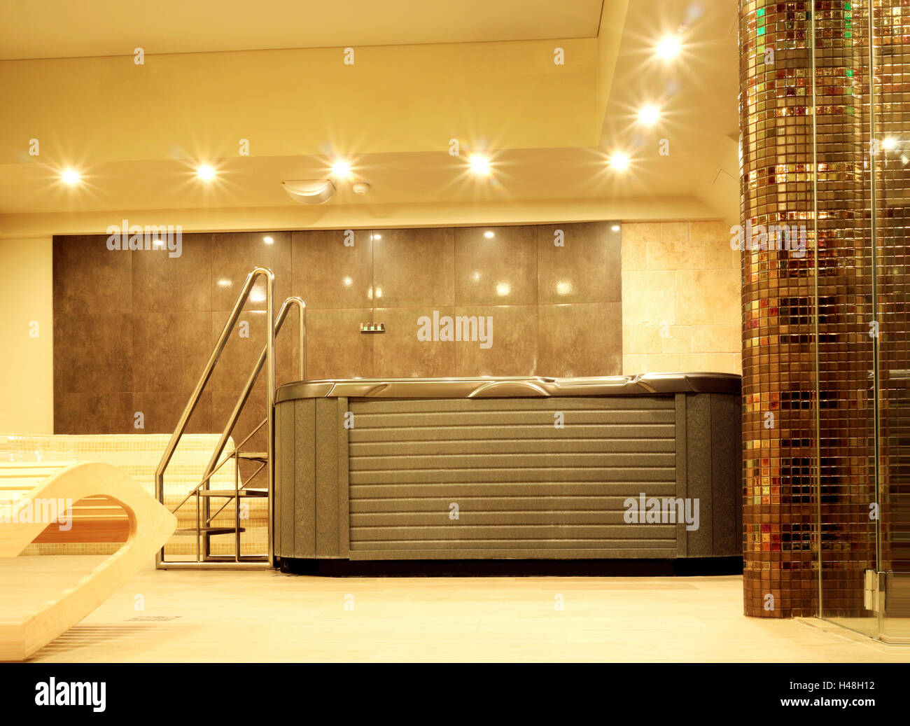 Indoor jacuzzi with metal stairs in a mosaic walled bathroom, in relaxing ambient light - Stock Image