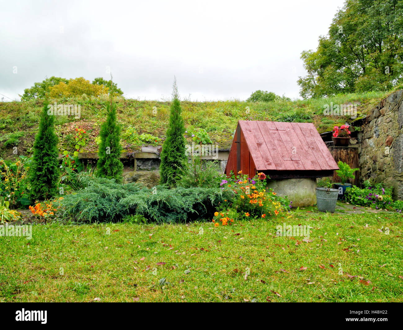 traditional old water well with wooden roof in an autumn country garden - Stock Image