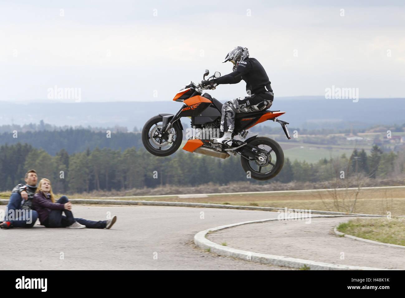 Motorcyclist, motorcycle, KTM, fun bike, jump, amazed couple, - Stock Image