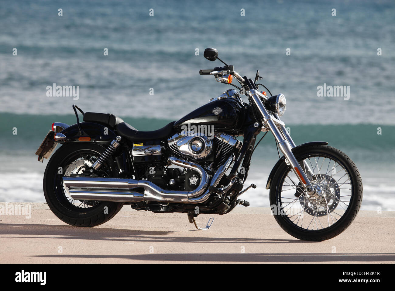 Motorcycle, Cruiser, Harley Davidson Wide Glide, black, sea in the background, side standard right, - Stock Image