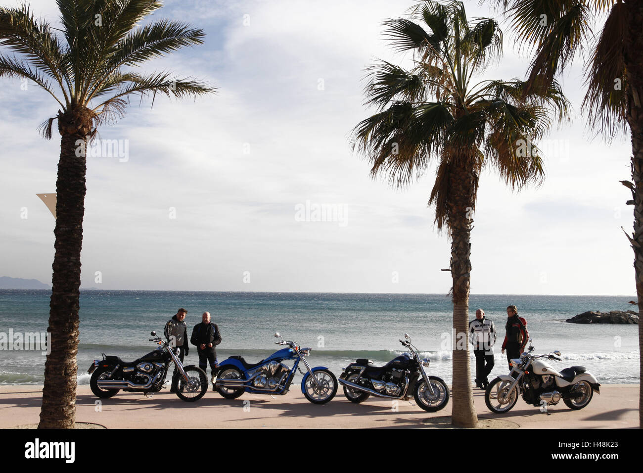 four motorcycles, cruisers, beach, palms, South of France, - Stock Image