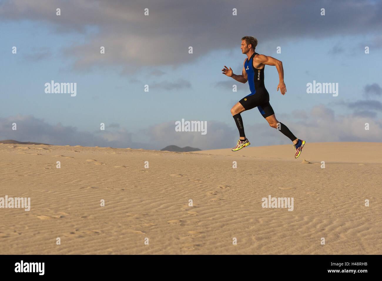 Runner sprints in Sand dune Fuerteventura, - Stock Image
