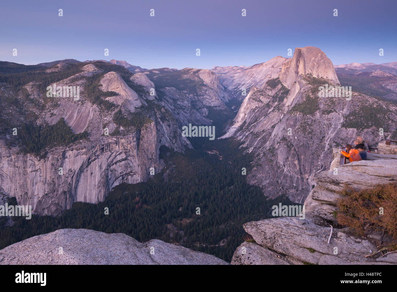 Tourists viewing Half Dome and Yosemite Valley from Glacier Point, Yosemite National Park, California, USA. Autumn - Stock Image