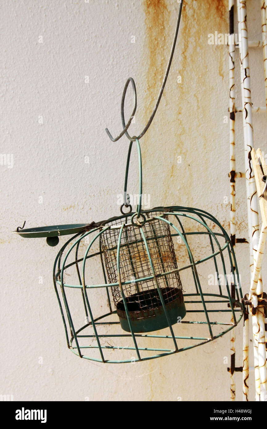 Wall of a house, feed cage, empty, cage, feed dispenser, old, rusty, traces of usage, object photography, nobody, - Stock Image