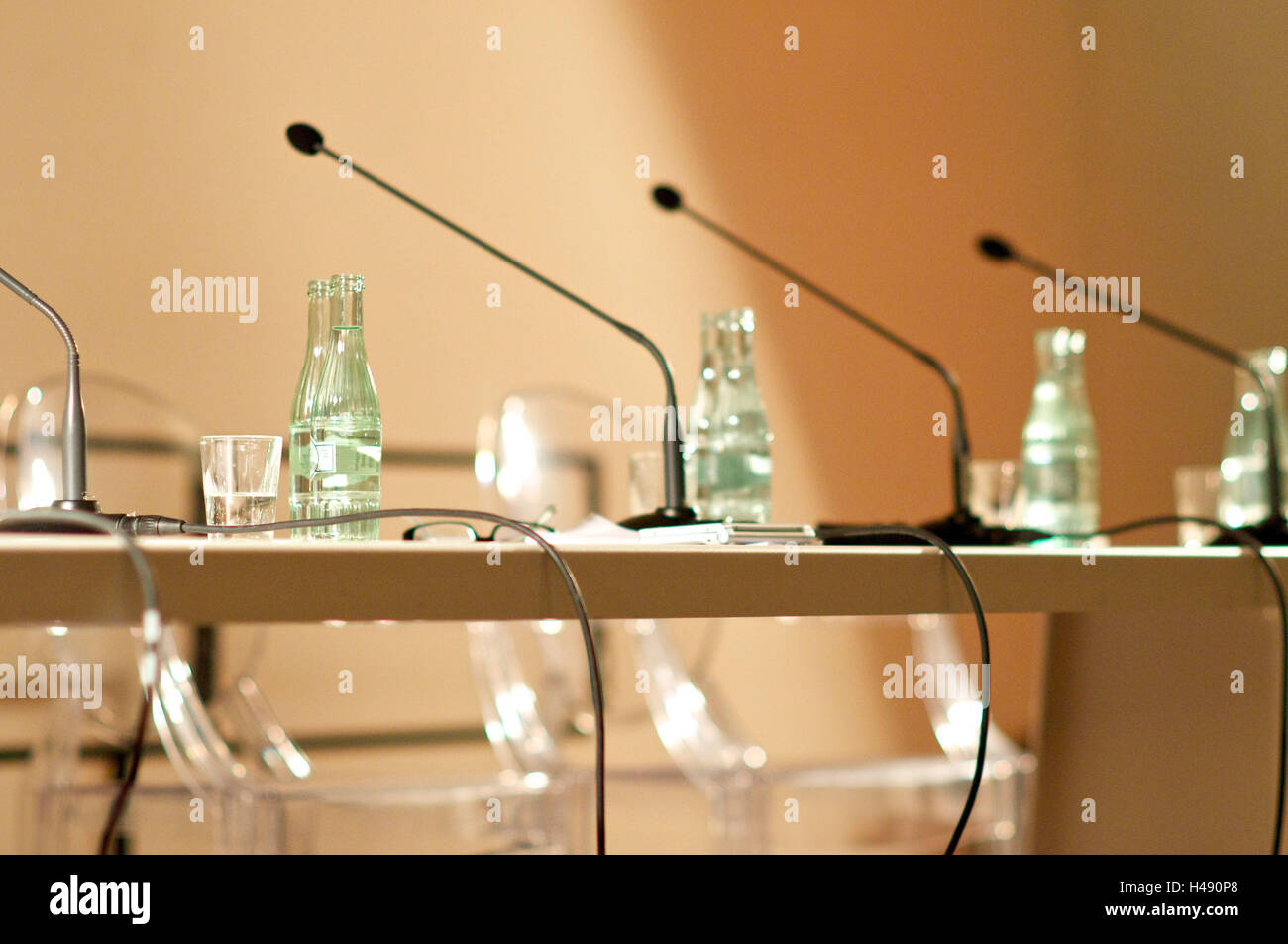 Conference table, microphones, water bottles, - Stock Image