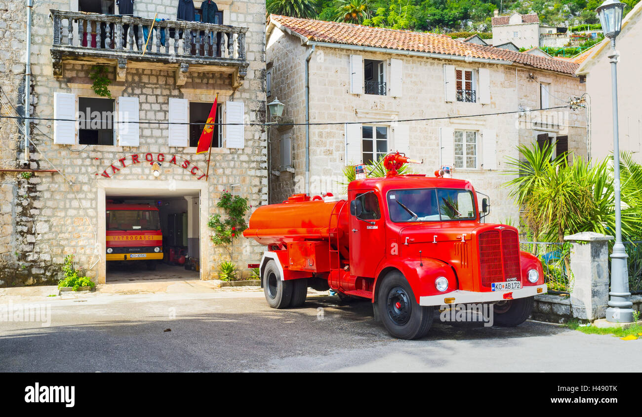 The bright red retro fire truck parked in the yard of the fire station, located on the city promenade, Perast Stock Photo