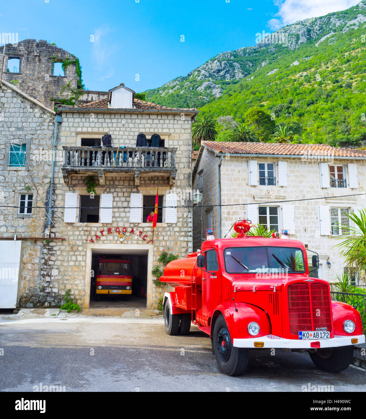The fire station, located in the old house on the city promenade, with the red fire truck next to it, Perast Stock Photo