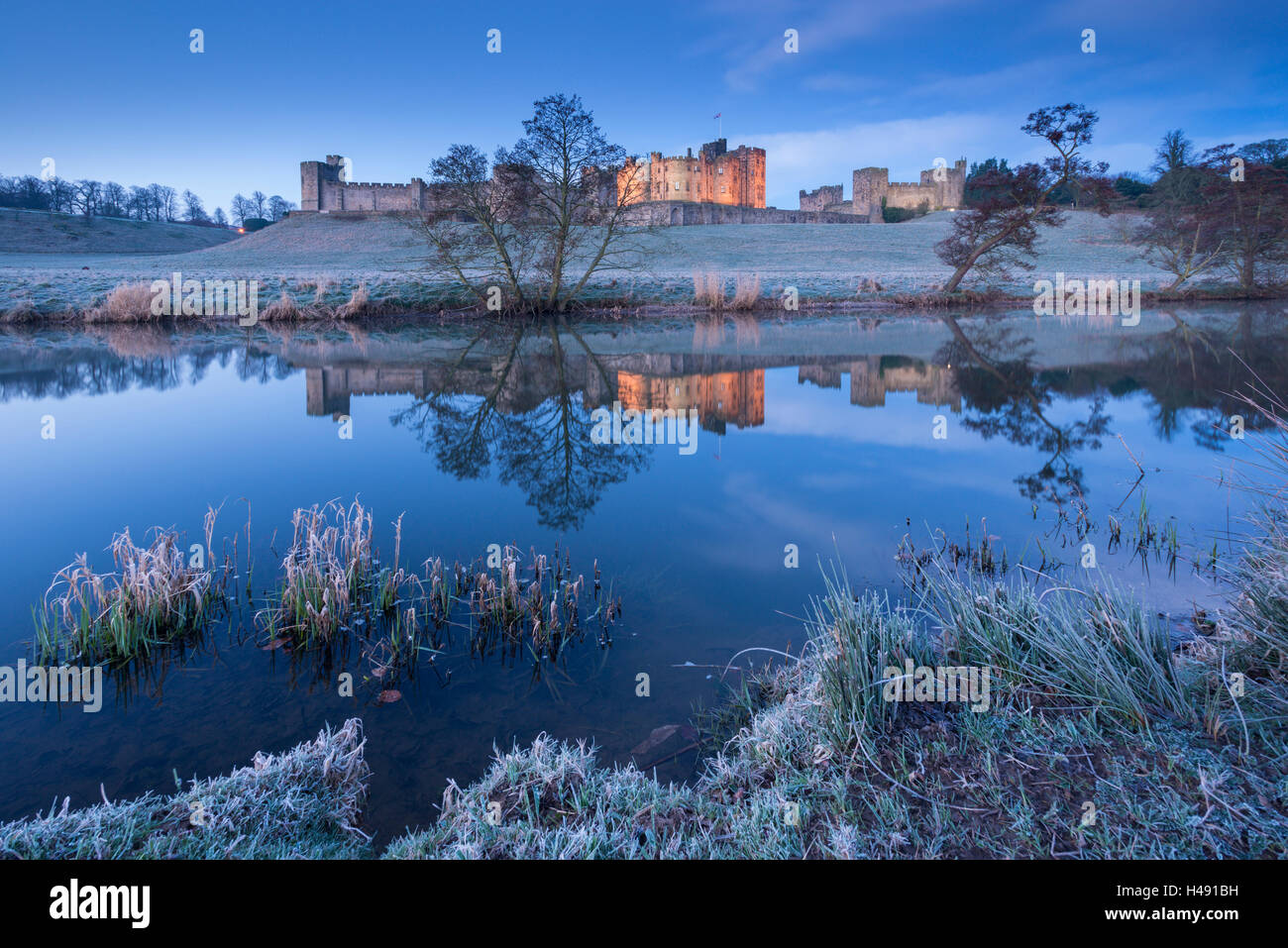Alnwick Castle reflected in the River Aln on a frosty winter morning, Northumberland, England. Winter (March) 2014. - Stock Image