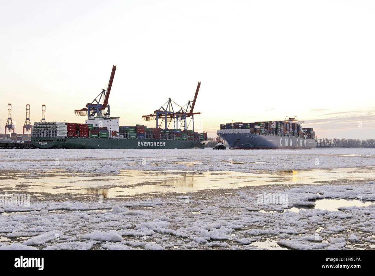 Container ship doing a turning manoeuvre, ice drift, floes floating on the Elbe, harbour cranes, Övelgönne, Hanseatic Stock Photo