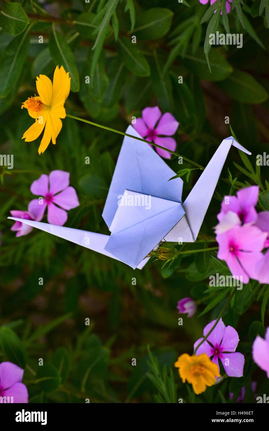 Origami hummingbird crane on beautiful stock photos origami origami hummingbird and crane on beautiful flowers in full spring in a litle garden izmirmasajfo
