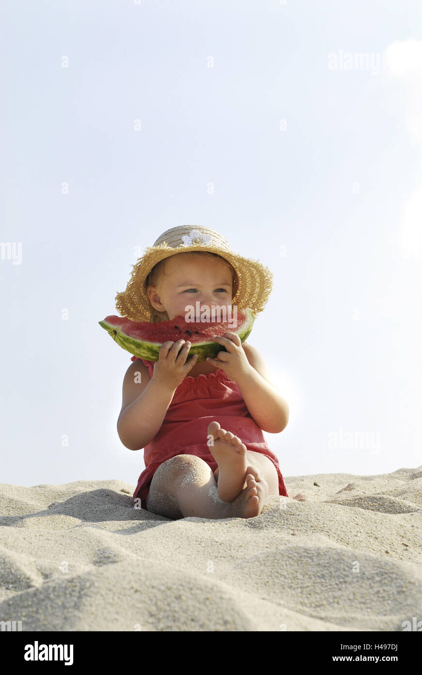 Girls, beach, sit, eat melon, - Stock Image