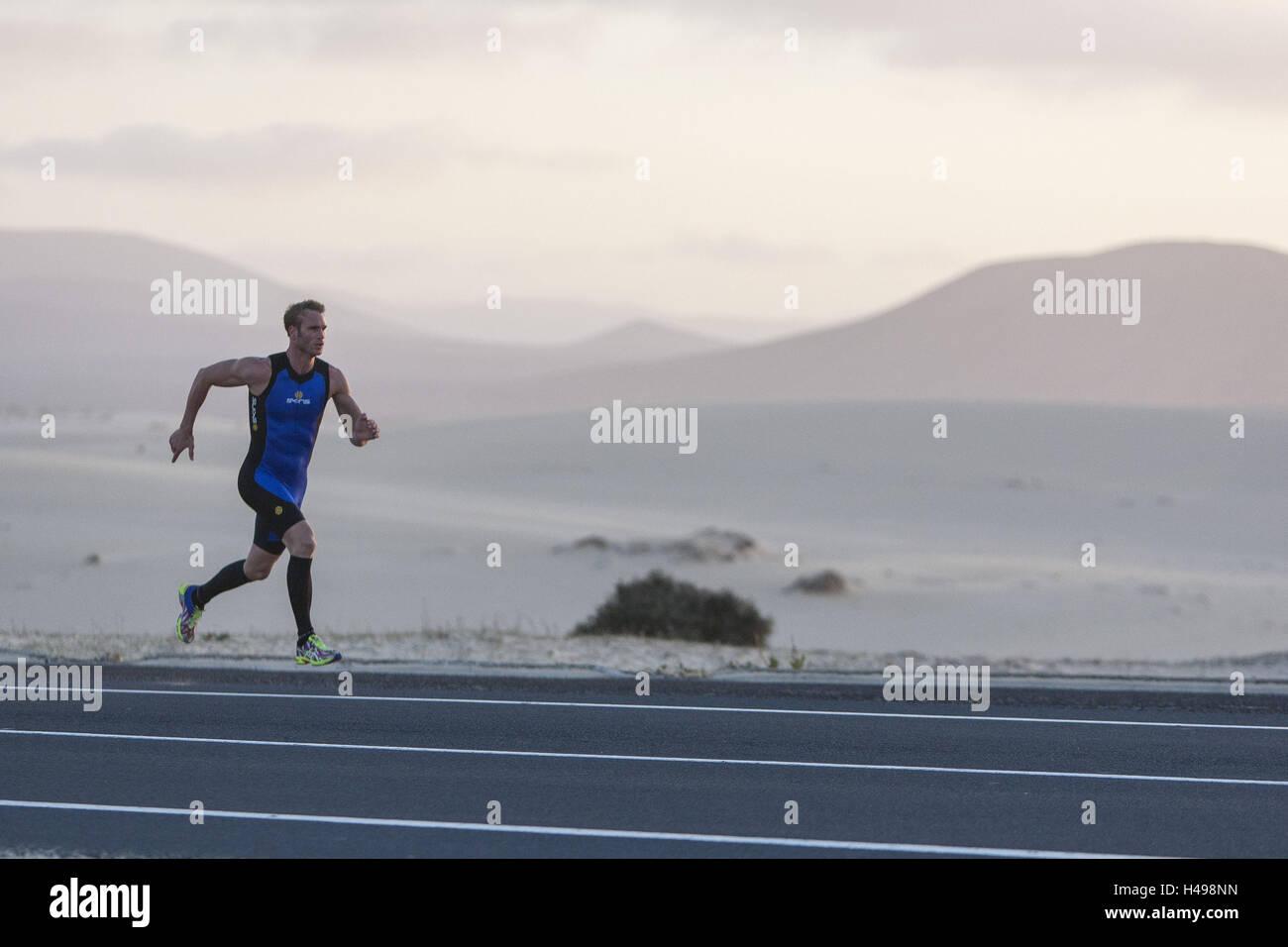 Runner sprints on asphalt road between the Sand dunes Fuerteventura, - Stock Image